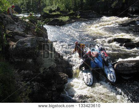 KOLA PENINSULA RUSSIA - AUGUST 11 - Team of men transported inflatable catamaran at rough river in Kola Peninsula on August 11 2008.