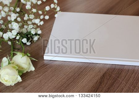 Blank white book journal wedding guestbook notebook mockup. Object for design and branding. White flowers and wooden texture perspective view.
