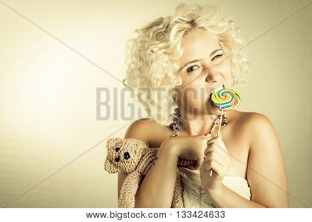 Blonde girl with colorful lollipop and bear toy. Woman biting lollipop and holding toy with squinting eyes.
