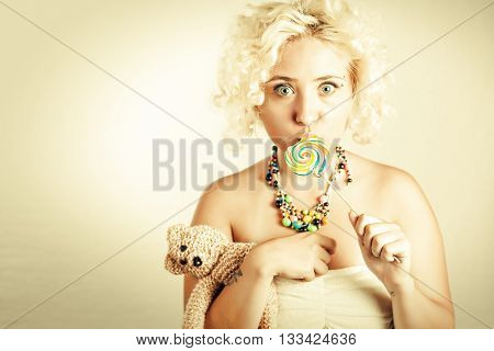 Blonde girl with wide open eyes holding colorful lollipop in one hand and bear toy in other hand. Woman kissing colorful lollipop.