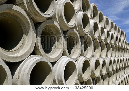 Stacked rows of oncrete drainage pipes for industrial building construction.