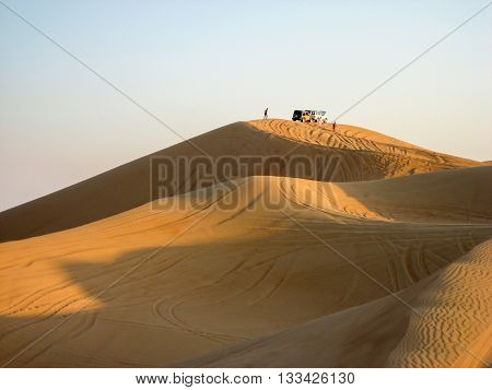 Large yellow desert sand dunes to the wheel tracks at sunset. On the horizon silhouettes of cars and people.