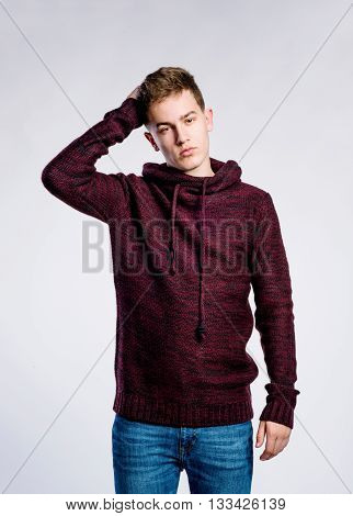 Teenage boy in jeans and burgundy red sweater, young man, scratching head, studio shot on gray background