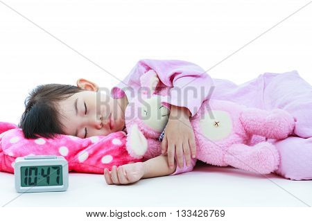 Healthy children concept. Asian child with doll sleeping peacefully. Adorable girl in pink pajamas taking a nap with alarm clock in foreground. On white background.