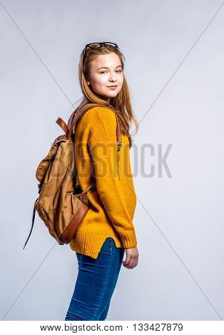 Teenage girl in jeans, yellow sweater, with backpack on back, young woman, studio shot on gray background
