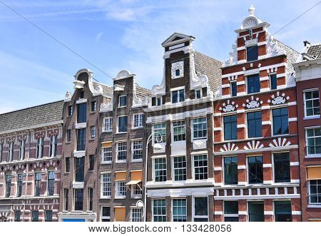 Dutch houses at a canal in Amsterdam. View to historic facades of cobblestone and stucco.