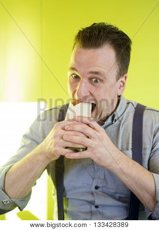 Man eats a sandwich in cafeteria.  Fastfood.