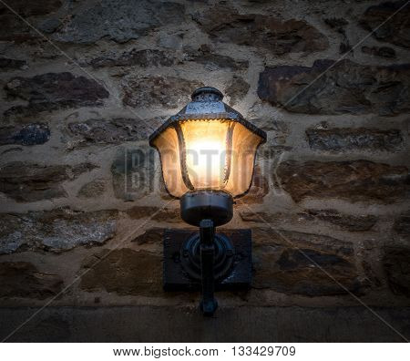 electric lantern on the stone wall .