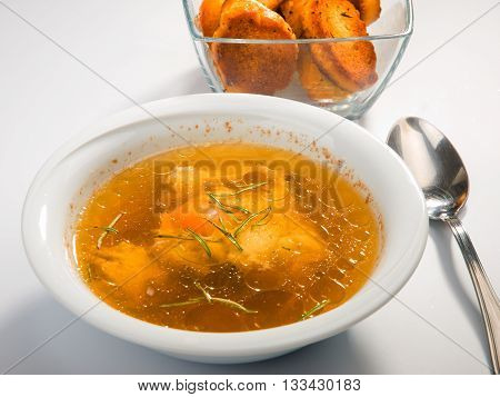 Plate of poached egg soup. Baked bread on background. Horizontal shot