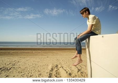 Teenager one on the seashore. Loneliness concept/