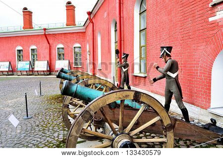 SAINT PETERSBURG RUSSIA - MAY 27 2016. Old artillery guns near the Naryshkin bastion of Peter and Paul fortress with wax statues of Russian soldiers dressed in the form of the 19th century