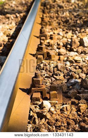 Close up view of steel railroad track with corroded metal bolts and surrounded by aged stones