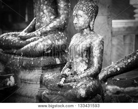Black annd white Buddha statue with golden leaf.