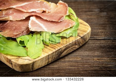 Refreshments of sliced Spanish ham and arugula is lying on a wooden desk of olive tree. Edited as a vintage photo with dark edges. Horizontally.