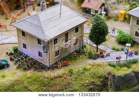 The layout of the village landscape. Small house front gardens with flowers children and the elderly.