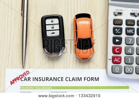 Top view of approved car insurance claim form with car key and car toy on wooden desk