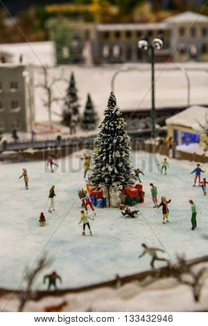 Layout winter outdoor Christmas ice rink. People are skating around the Christmas tree in the urban landscape.
