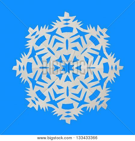Snowflake cut from paper and lies on blue background
