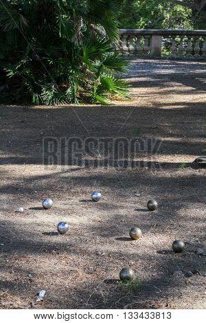 Steel balls for a game of boules on the ground among light and shadow in a subtropical park.