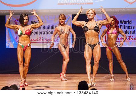 MAASTRICHT THE NETHERLANDS - OCTOBER 25 2015: Female bodybuilders Gerbel Mikk and Sonja den Breems-Tanamal flex their muscles and show their best physique in a front double biceps pose on stage at the World Grandprix Bodybuilding and Fitness