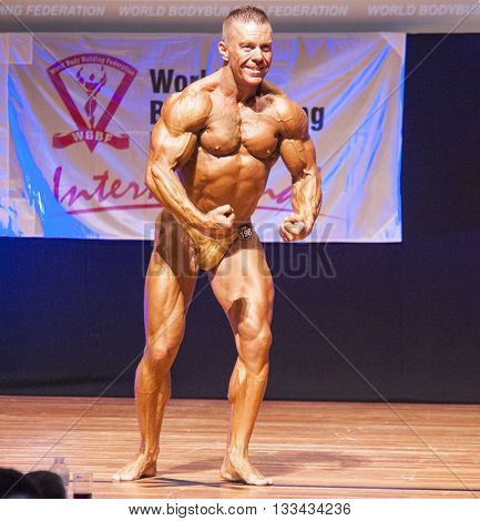 MAASTRICHT THE NETHERLANDS - OCTOBER 25 2015: Male bodybuilder flexes his muscles and shows his best physique in a most muscular pose on stage at the World Grandprix Bodybuilding and Fitness of the WBBF-WFF
