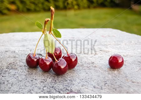 Sweet ripe cherry in the garden on stone