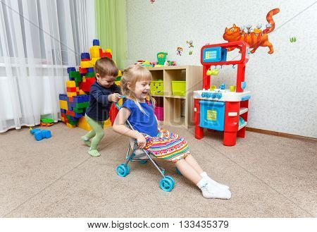 Two Happy Children Play With Toy Stroller In Daycare