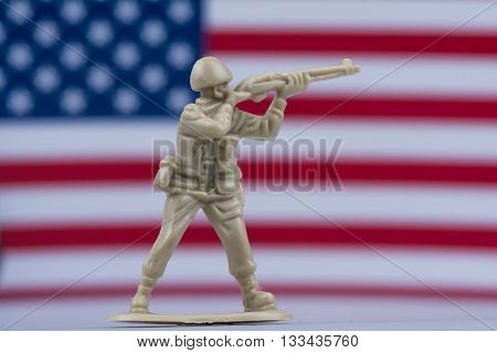 Toy soldier aiming gun in front of American Flag