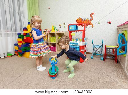 Two Children Play With Plastic Rings In Kindergarten