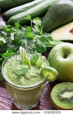 A glass of green vegetable smoothie near ingredients celery avocado cucumber kiwi apple herbs on wooden background. Green vegetable smoothie and ingredients. Vertical. View from above.