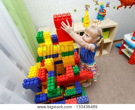 Persistent Little Girl Building Big Block Tower In Daycare