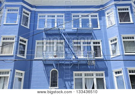 The colorful and unique architecture and fire escape on the exterior of an apartment in a San Francisco's neighborhood.