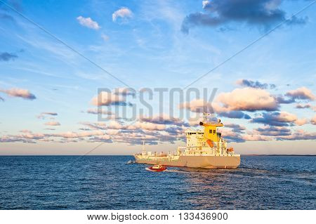 Pilot boat maneuvers next to tanker ship on sea.