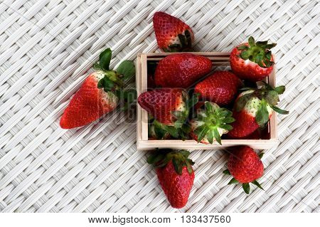 Heap of Fresh Ripe Strawberries in Wooden Tray closeup on Wicker background. Top View