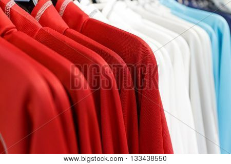 red and white and blue shirt hanging on for sale soft focus focus at red shirt