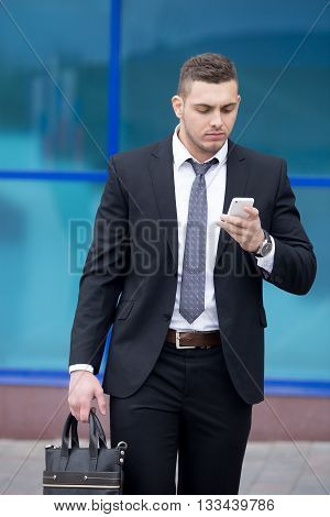 Portrait Of Business Man Looking At Smartphone Screen With Focused Expression