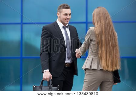 Business Man And Woman Shaking Hands On The Street