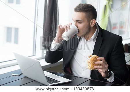 Portrait Of Young Businessman Working On His Lunch Time In Modern Coffee Shop