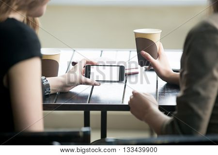 Woman Hands Holding Telephone With White Blank Screen In Cafe. Close-up