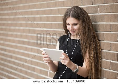 Waist portrait of young woman standing in the street beside brick wall listening music online with headphones from tablet. Happy beautiful woman using electronic device looking at screen. Copy space