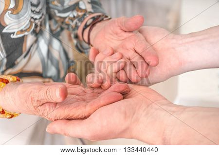 Senior Or Eldery Assistance Concept. Young Man Holds Hands Of Se