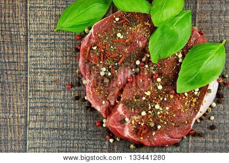 Two raw sirloin steaks sprinkled with spices and fresh basil leaves on wooden background flat view from above