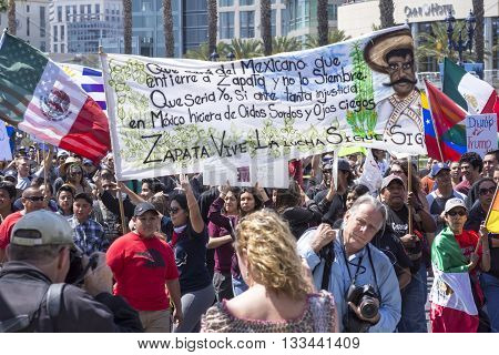 SAN DIEGO USA - MAY 27 2016: A huge crowd gathers to march at an anti-Trump protest in San Diego while carrying a large banner in memory of the revolutionary Emiliano Zapata.