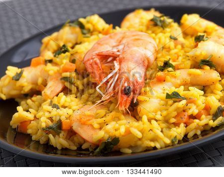 Seafood risotto with shrimps curry and herbs. Vertical shot tilted. Close up
