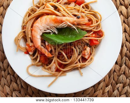 Italian spaghetti pasta with shrimps tomatoes and basil. Shot from above horizontal shot