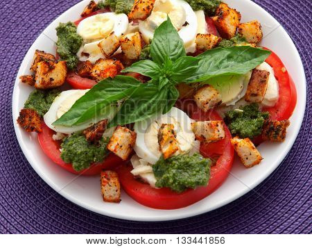 Healthy salad with tomatoes boiled eggs pesto and croutons. Horizontal shot