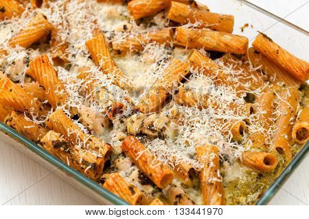 Baked Penne pasta with parmesan cheese in caserole. Shot from above. Tilted view horizontal shot