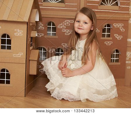 Little girl with long blond hair in elegant white dress on a background of a Dollhouse