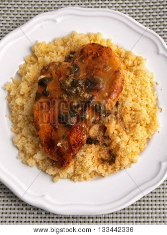 Couscous with curry chicken fillet and mushrooms sauce. Shot from above. Vertical shot
