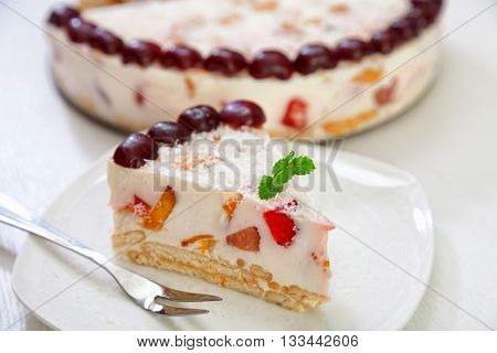 Cake with strawberries gelly yogurt and cherries isolated on white background in a plate